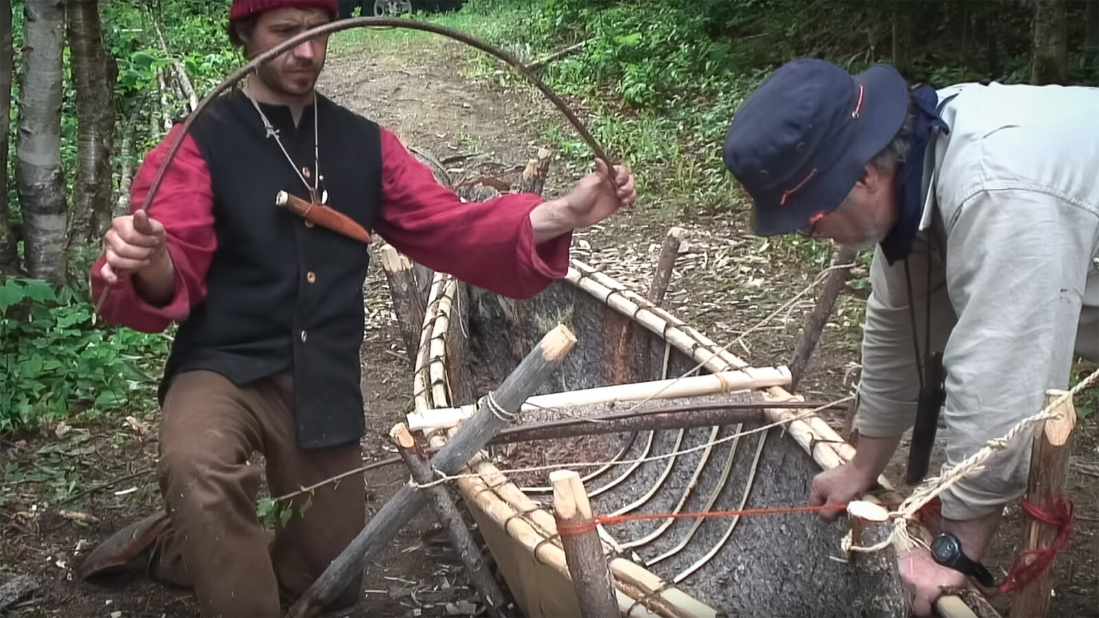 Two men making a spruce bark canoe